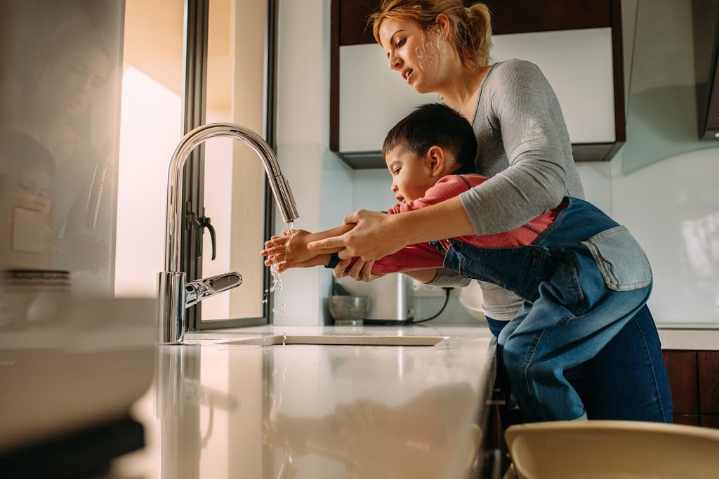 Mother and son washing hands in sink