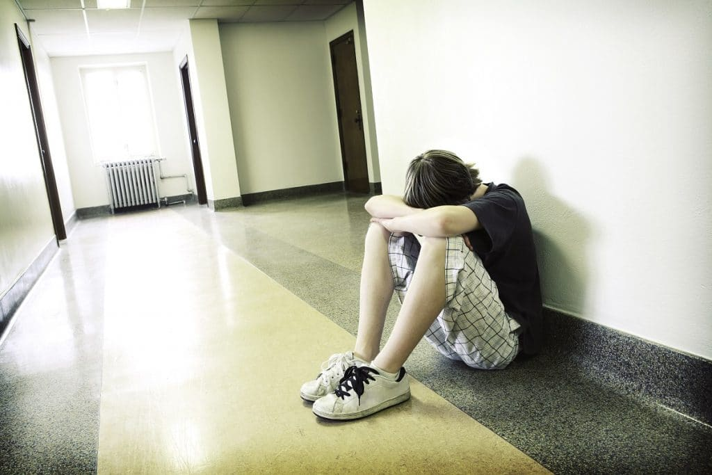 Depressed student sitting on floor in corridor with hands and face on knees.